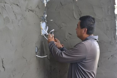 A worker attached to Eco Housing Inc, installing wires for electricity.