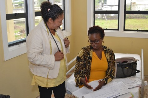 Dr. Ertenisa Hamilton examines Maternal and Child Health records with Community Health Worker (CHW) Wavney Austin at the Four Miles Health Post.