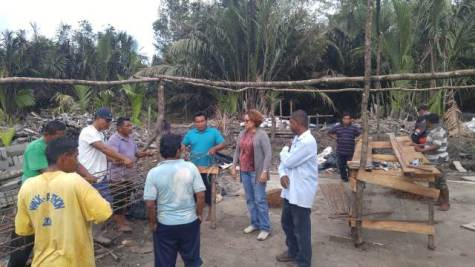 Minister within the Ministry of Indigenous Peoples' Affairs, Valarie Garrido- Lowe interacts with labourers.