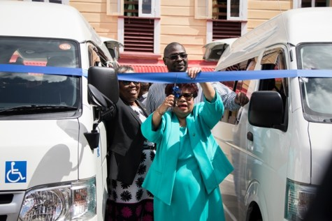 Minister Amna Ally is joined by her team as she cuts the ribbon at the commissioning for the buses in the compound of the Palms Geriatric Facility.