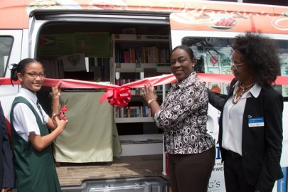 …(from right to left)Rotary District Governor, Dominique Venre, Minister of Education, Dr. Nicolette Henry and a student representative from the Bishop High School preparing to cut the ribbon of the Bookmobile.