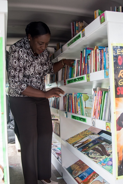 Minister of Education, Dr. Nicolette Henry checking out the books onboard the Bookmobile.
