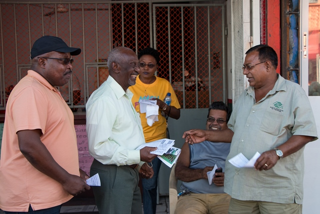 Minister within the Ministry of Social Protection, Keith Scott interacting with business persons at the Bourda Market.