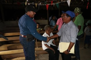 Minister of Indigenous Peoples' Affairs, Sydney Allicock interacting with a resident of Yurong Paru.