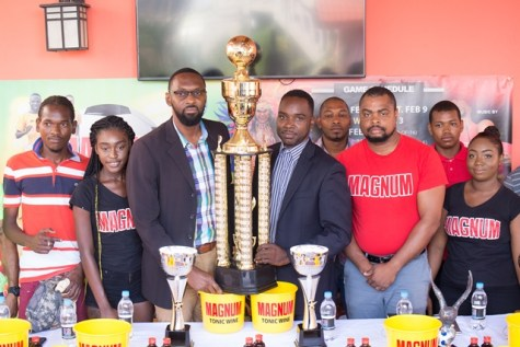 (left to right) Director of Sports Christopher Jones, Legacy Entertainment spokesperson Esan Griffith and Magnum Brand Coordinator Edison Jefford with team representatives and the Magnum girls, display the Mash Cup' Inter-Ward' futsal championship trophy.