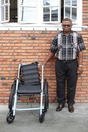 Leslie Vanooten receiving the wheelchair on behalf of his mother, Iyona Smith.