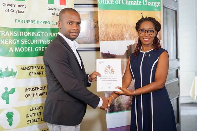 Head, Office of Climate Change (OCC), Janelle Christian hands over of the reports to Mayor of Bartica, Gifford Marshall.