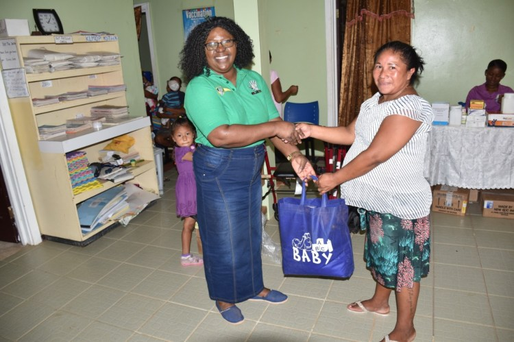 Minister within the Ministry of Public Health, Dr. Karen Cummings hands over a package containing medical items to a mother at Sand Creek