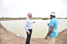 Minister Dominic Gaskin and the aquaculture farmer Ronald Arjune in discussion about the operations at the farm.