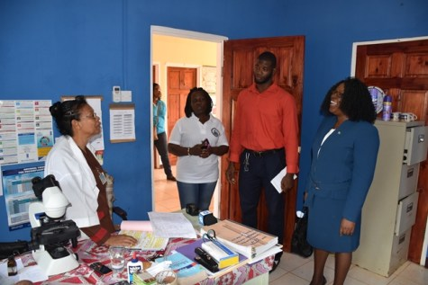 Microscopist, Nathalie Singh interacts with Minister within the Ministry of Public Health, Dr. Karen Cummings.