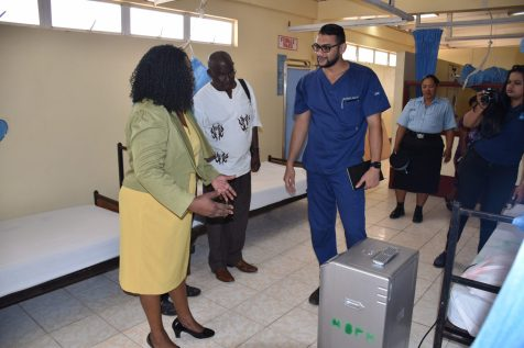 Minister within the Ministry of Public Health, Dr. Karen Cummings being briefed on the uses of the oxygen concentrator