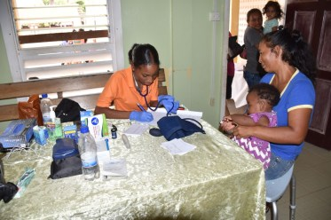 A mother and baby meet a member of the medical team today at Sand Creek