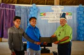 Minister of Indigenous Peoples' Affairs, Sydney Allicock handing over the computer and printer to the two brothers Bernie Robertson and Ali Joel