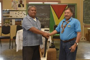 Minister of Indigenous Peoples' Affairs, Sydney Allicock handing farming tools to Toshao of Toka, Eugene Issacs