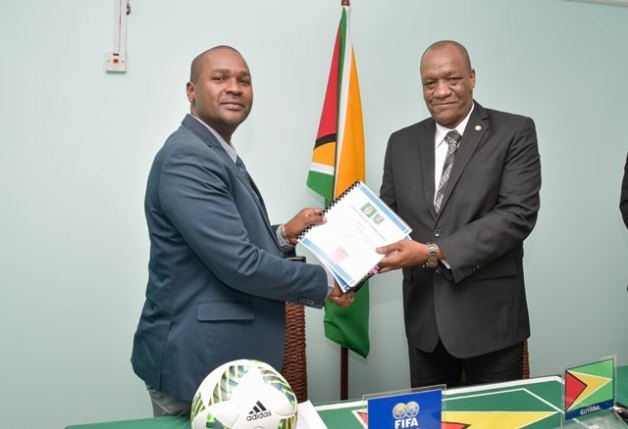 Minister of State, Mr. Joseph Harmon hands over a copy of the Memorandum of Understanding to President of the Guyana Football Federation, Mr. Wayne Forde.