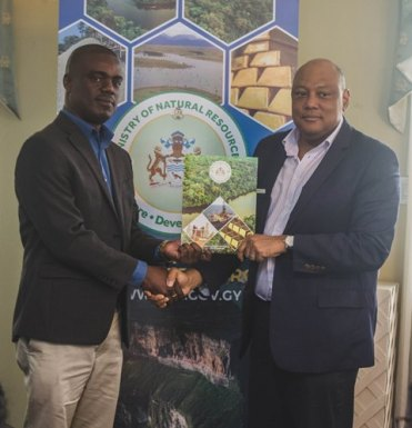 [In the photo, from left to right] Senior Technical Director of Conservation International Guyana, Curtis Bernard receiving the MOU from Minister of Natural Resources, Raphael Trotman.