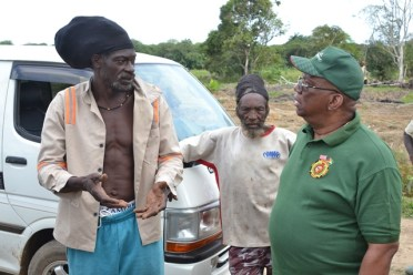 Minister of Finance, Winston Jordan interacts with a Buxton Farmer.