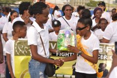 A young cancer survivor receiving a token from the Giving Hope Foundation