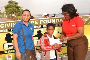 GUYOIL representatives present token to young cancer survivor