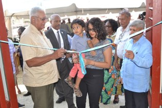 Minister Holder witnesses the cutting of the ribbon by a child of the community.