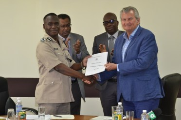 Commissioner of Police, Leslie James receives the Strategic Plan from British Security Advisor, Russell Combe.