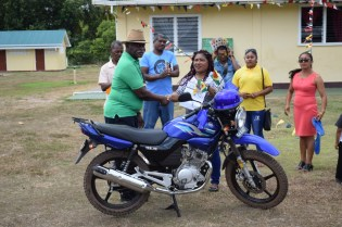 Minister of Citizenship, Winston Felix hands over a motorcycle to Secretary of the Block Making Committee, Mercie Stephna
