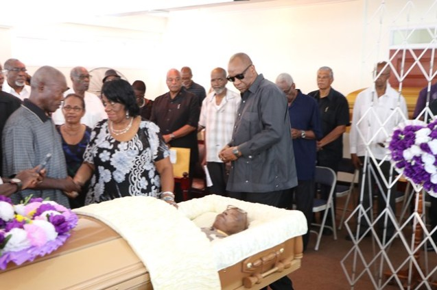 Minister of State, Joseph Harmon viewing the body.