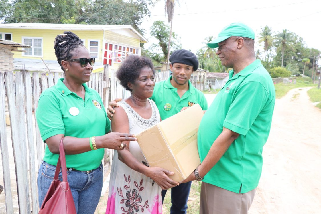 Minister of State, Joseph Harmon handing over one of the lights to a resident of Blueberry Hill, Ruth Davis