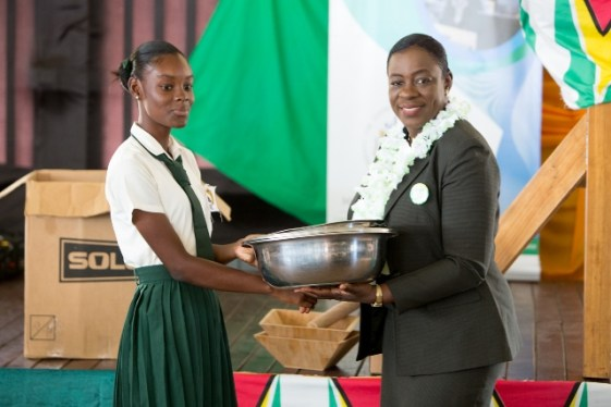 Minister of Education, Dr. Nicolette Henry handing over Home Economics equipment to a student of the Canje Secondary School.