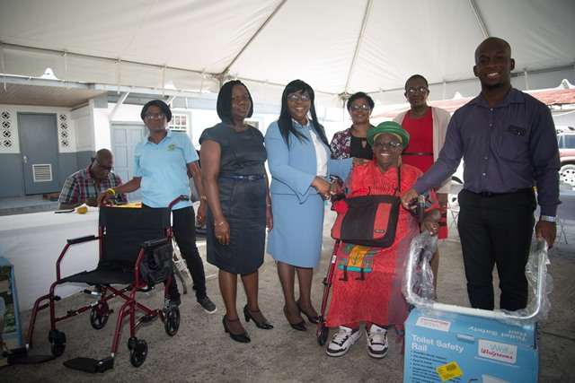 Minister within the Ministry of Public Health, Dr. Karen Cummings hands over wheelchair and walker to pensioner Maylene Fingall.