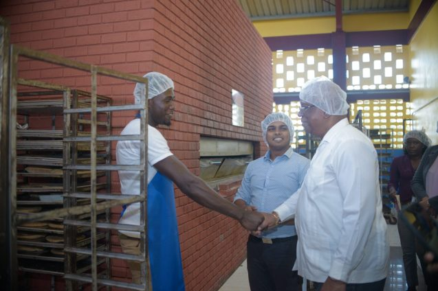 Minister of Finance, Winston Jordan greets one of the bakers at Demerara Bakery