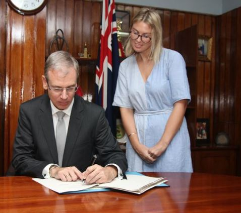 His Excellency Anton Ojala sign the Air Services Agreement and Ms. Ruth Delany.