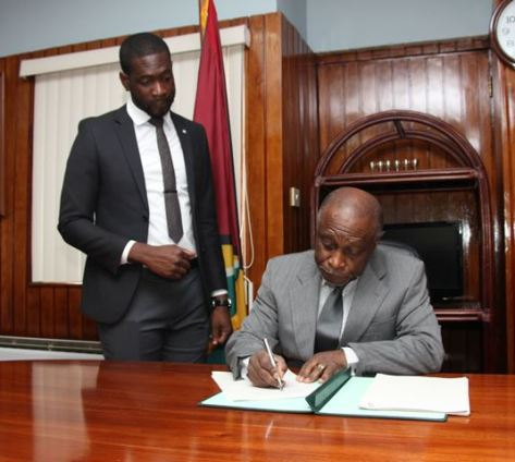 The Foreign Minister signs the Agreement while Foreign Service Officer, Mr. Royston Alkins looks on.
