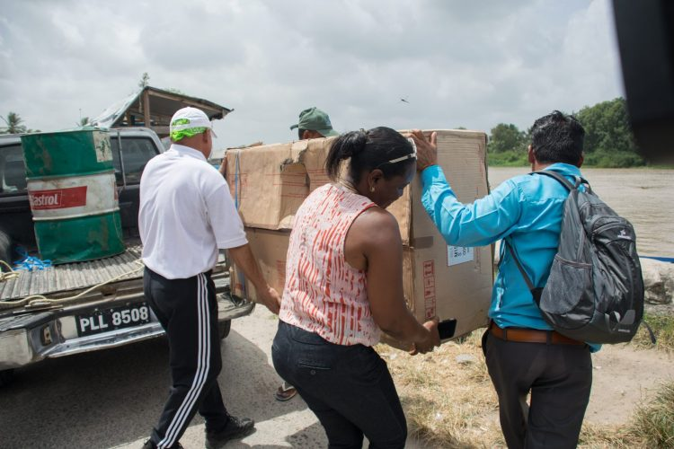 Minister of Social Cohesion, Dr. George Norton and team assisting Toshao in transporting new engine