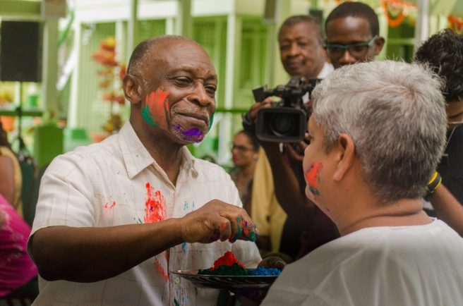 Minister of Foreign Affairs, Carl Greenidge who is currently performing the functions of president, puts powder on Minister within the Ministry of Finance, Jaipaul Sharma during Phagwah Celebrations at State House on Sunday