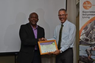 Director General of the Department of Tourism in the Ministry of Business, Donald Sinclair presents the award to Minister of Business, Dominic Gaskin