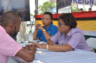 Minister of Public Telecommunications, Catherine Hughes interacting with a citizen.