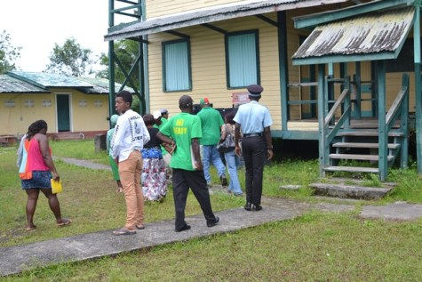 Minister of Finance, Winston Jordan with residents, on-site at the school's compound.