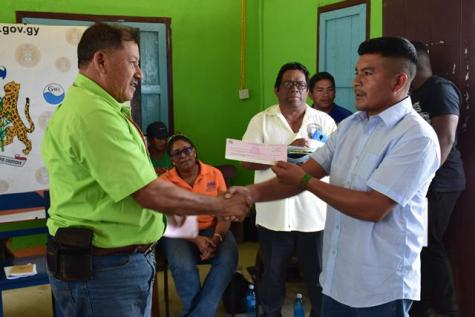 Toshao of Kopinang, Fred Bill receiving a cheque from Minister of Indigenous Peoples' Affairs, Sydney Allicock.