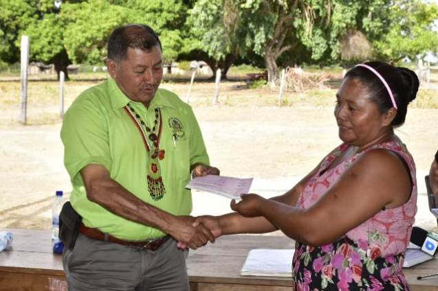 Councillor, Mary Fernandes of Patarinau Village, receiving a cheque from Minister of Indigenous Peoples' Affairs, Sydney Allicock.