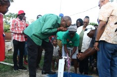 Minister of State, Joseph Harmon and residents taking turn to take a drink of water at one of the 29 standpipes commissioned on Saturday at the Durban Backlands.
