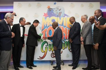 Minister of Foreign Affairs, Carl Greenidge who is currently performing the functions of Prime Minister, cuts the ribbon to mark the official opening of Movietown Guyana with MovieTowne's Chairman, Dereck Chin