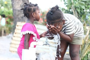 Young girls washing their faces at one of the standpipes commissioned.