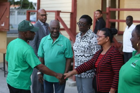 Minister of Foreign Affairs, Carl Greenidge, who is currently performing the functions of president, greets staff at the Campbellville Secondary School before his constituency meeting, as Minster within the Ministry of Social Protection, with responsibility for Labour, Keith Scott looks on.