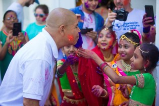 Minister of Social Cohesion, Dr. George Norton, is greeted with gulal/abrak by students of the Swami Vivekananda Cultural Centre upon his arrival for Holi/ Phagwah celebrations, at the Swami Vivekananda Cultural Centre.