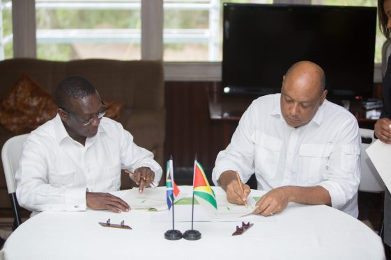 """Minister of Natural Resources, Raphael Trotman and South Africa's Deputy Minister of Mineral Resources, Godfrey Oliphant signing the """"Declaration of Intent"""" at Watooka House in Linden"""