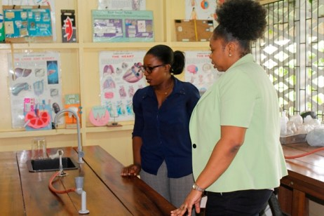 Ms. Roberts inspecting the science laboratory of the Brickdam Secondary School along with a teacher.