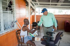 Minister of Indigenous Peoples' Affairs, Sydney Allicock interacting with a resident of East La Penitence, Randolph Charles.