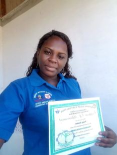 A proud Sinclair displays her certificate after completing a course in Supervisory Management.