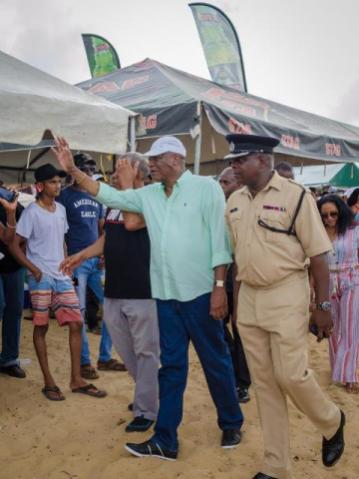 Minister of State, Joseph Harmon greets spectators at the Bartica Regatta.